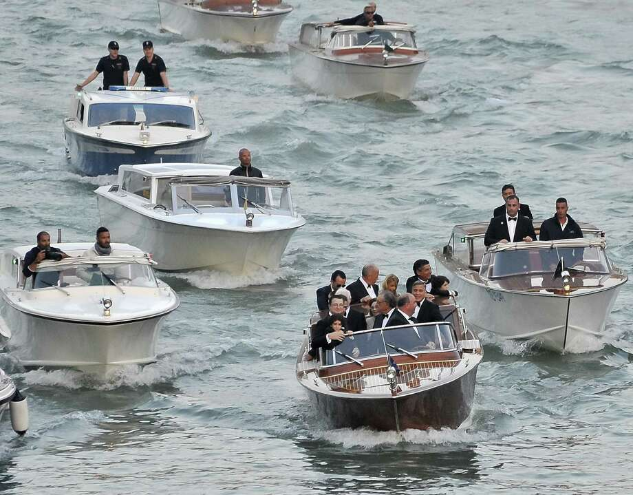 Joined by family and friends, actor George Clooney (center boat) cruises down the Grand Canal on his way to the Aman hotel, where he and attorney Amal Alamuddin were married. Photo: Luigi Constantini / Associated Press / AP