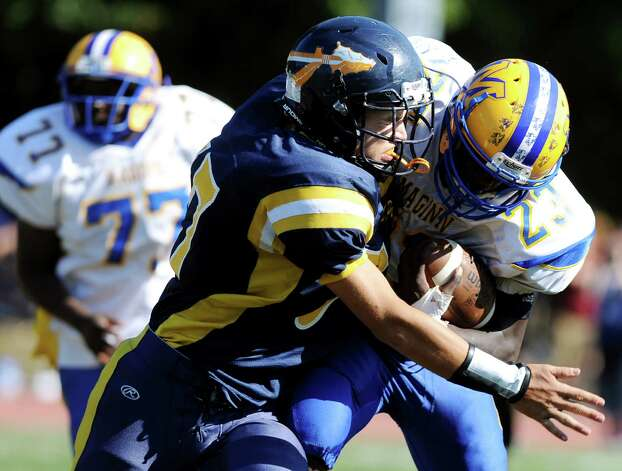 Averill Park's Daquan Gordon, center, brings down Bishop Maginn's Ky'Ere Tillery during their football game on Saturday, Sept. 27, 2014, at Averill Park High in Averill Park, N.Y. (Cindy Schultz / Times Union) Photo: Cindy Schultz / 00028729A