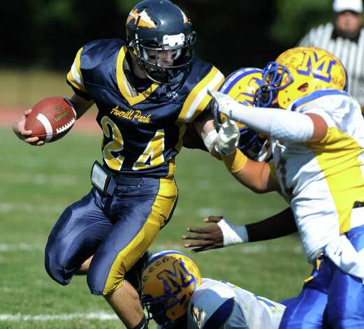 Averill Park's Nick Haase, left, fights off Bishop Maginn's defense during their football game on Saturday, Sept. 27, 2014, at Averill Park High in Averill Park, N.Y. (Cindy Schultz / Times Union) Photo: Cindy Schultz / 00028729A