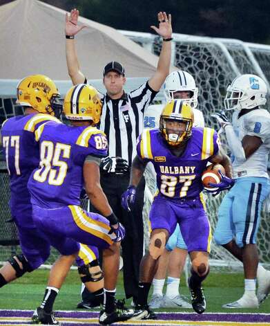 UAlbany's #87 Cole King is congratulated by teammates after pulling in a touchdown pass during Saturday's game against  Columbia at Bob Ford Field in Albany, NY.  (John Carl D'Annibale / Times Union) Photo: John Carl D'Annibale / 00028710A