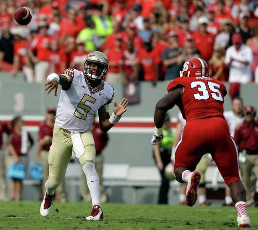 Florida State quarterback Jameis Winston (5) throws a pass as North Carolina State's Kentavius Street (35) rushes during the first half of an NCAA college football game in Raleigh, N.C., Saturday, Sept. 27, 2014. (AP Photo/Gerry Broome) ORG XMIT: NCGB104 Photo: Gerry Broome / AP