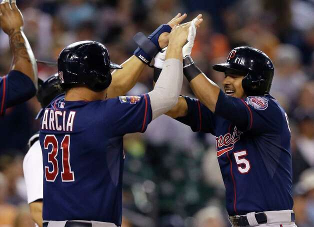 Minnesota Twins' Eduardo Escobar (5) is congratulated by teammate Oswaldo Arcia after his three-run home run during the eighth inning of a baseball game against the Detroit Tigers in Detroit, Saturday, Sept. 27, 2014. (AP Photo/Carlos Osorio) ORG XMIT: MICO117 Photo: Carlos Osorio / AP