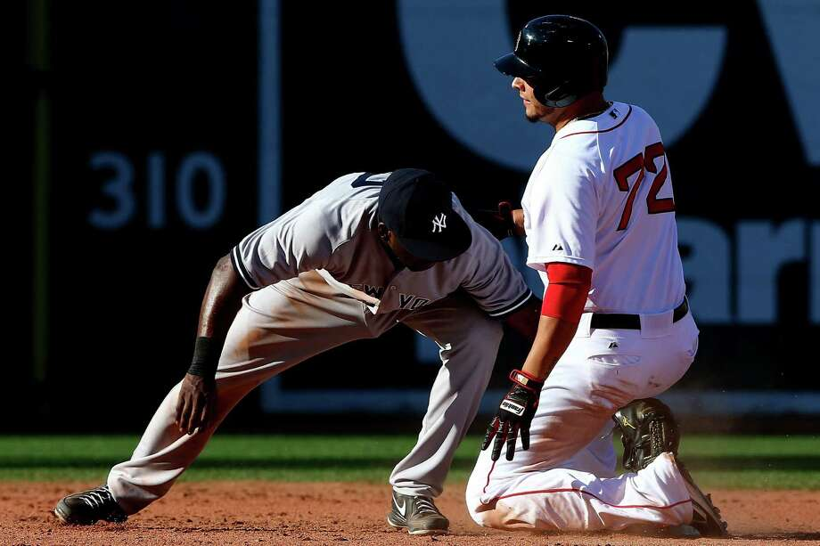 Boston's Carlos Rivero slides into second base with a double, beating the tag of the Yankees' Jose Pirela. Photo: Elsa / Getty Images / 2014 Getty Images