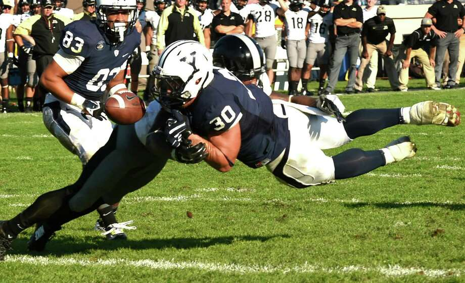 Yale running back Tyler Varga (right) scores a touchdown against Army cornerback Chris Carnegie and then loses the ball after crossing the goal line during a 49-43 overtime victory. Photo: Peter Hvizdak / New Haven Register / New Haven Register
