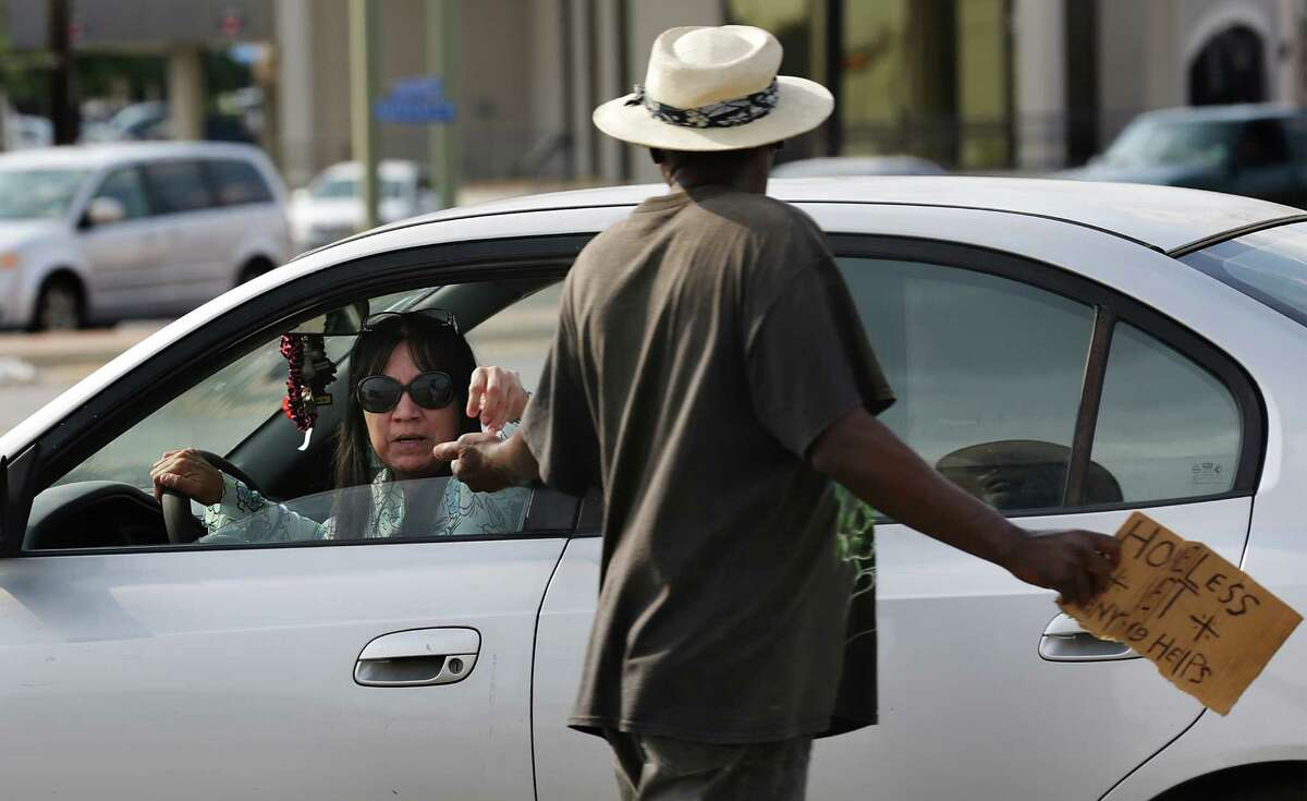 A motorist hands Earl Carrier, 61, a veteran who has been homeless for 15 years, some change as he panhandles at the corner of I410 and Fredericksburg Rd. Tuesday, September 23, 2014