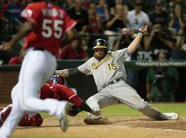 ARLINGTON, TX - SEPTEMBER 27: Roman Mendez #55 of the Texas Rangers runs in to cover home plate as Jonny Gomes #15 of the Oakland Athletics slides in safe against Robinson Chirinos #61 in the eighth inning at Globe Life Park in Arlington on September 27, 2014 in Arlington, Texas.  (Photo by Rick Yeatts/Getty Images)