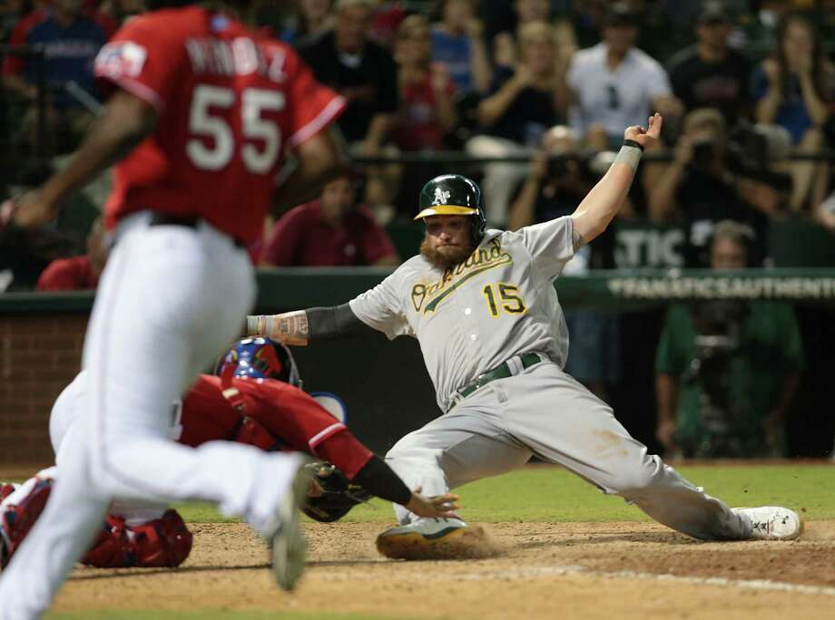 ARLINGTON, TX - SEPTEMBER 27: Roman Mendez #55 of the Texas Rangers runs in to cover home plate as Jonny Gomes #15 of the Oakland Athletics slides in safe against Robinson Chirinos #61 in the eighth inning at Globe Life Park in Arlington on September 27, 2014 in Arlington, Texas.  (Photo by Rick Yeatts/Getty Images) Photo: Rick Yeatts / Getty Images / 2014 Getty Images