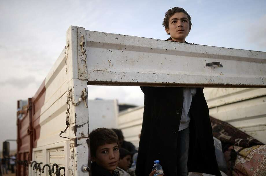 TOPSHOTS Syrian Kurds boys, fleeing an onslaught by the jihadist Islamic State (IS) group, sit in a truck as they cross the Syria Turkey border at the southeastern town of Suruc in Sanliurfa province, on September 27, 2014. Hundreds of Kurds broke yesterday through the Turkish border into Syrian territory to join Kurdish forces battling the advance of Islamic State (IS) militants around the Syrian town of Ain al-Arab.  AFP PHOTO/BULENT KILICBULENT KILIC/AFP/Getty Images Photo: Bulent Kilic, AFP/Getty Images
