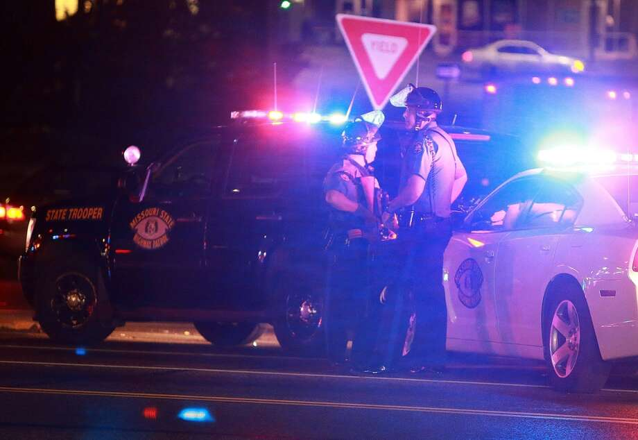 Missouri State Highway Patrol troopers stand on the side of the road Saturday night after a Ferguson police officer was shot. Photo: Christian Gooden / McClatchy-Tribune News Service / St. Louis Post-Dispatch