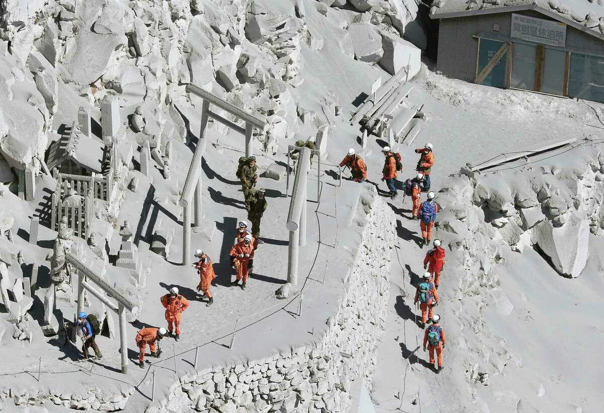 Firefighters advance to rescue climbers near the peak of Mount Ontake in central Japan, Sunday, Sept. 28, 2014. Mount Ontake erupted shortly before noon Saturday, spewing large white plumes of gas and ash high into the sky and blanketing the surrounding area in ash. Rescue workers on Sunday found more than 30 people unconscious and believed to be dead near the peak of an erupting volcano, a Japanese police official said. JAPAN OUT, MANDATORY CREDIT