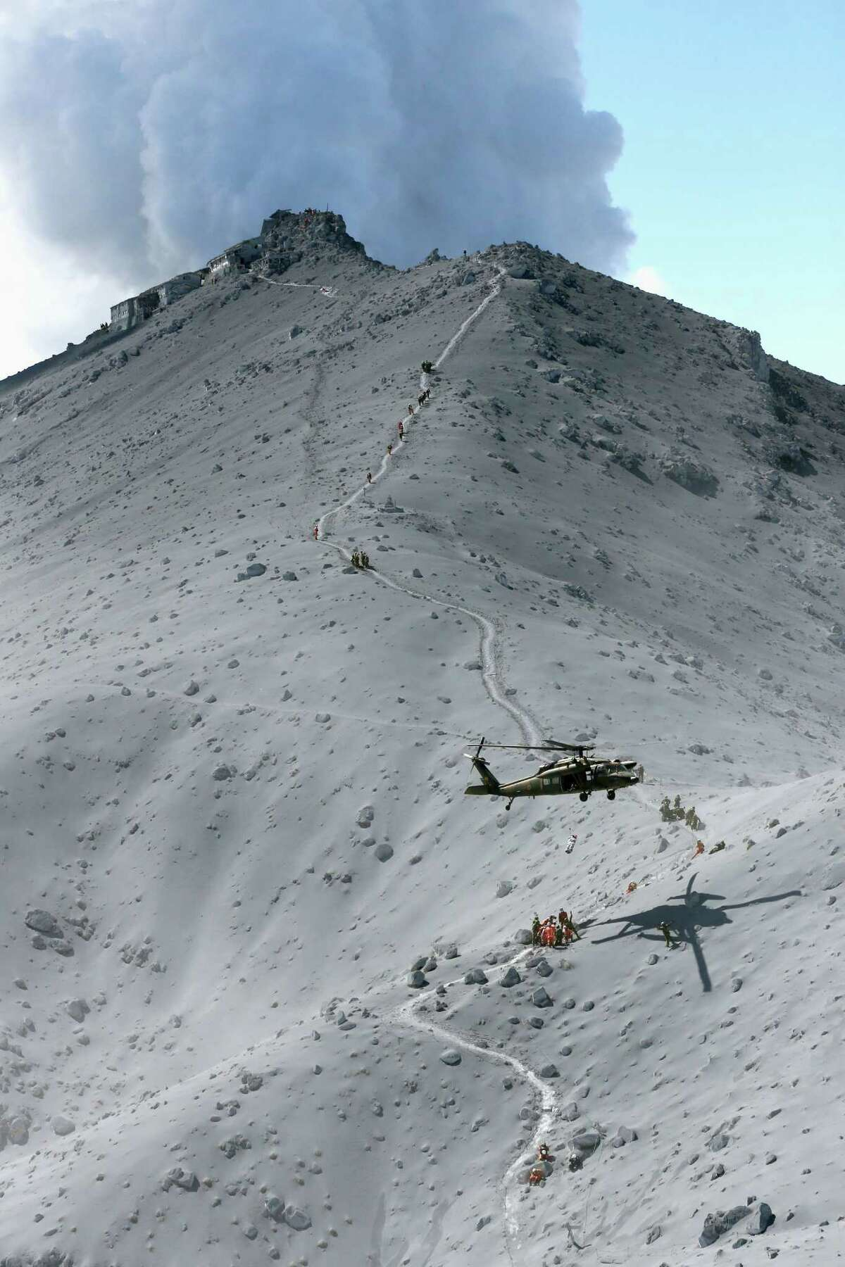 Firefighters and members of Japan's Self-Defense Forces conduct a rescue operation near the peak of Mount Ontake as plumes of smoke billow in central Japan, Sunday, Sept. 28, 2014. Mount Ontake erupted shortly before noon Saturday, spewing large white plumes of gas and ash high into the sky and blanketing the surrounding area in ash. Rescue workers on Sunday found more than 30 people unconscious and believed to be dead near the peak of an erupting volcano, a Japanese police official said. JAPAN OUT, MANDATORY CREDIT