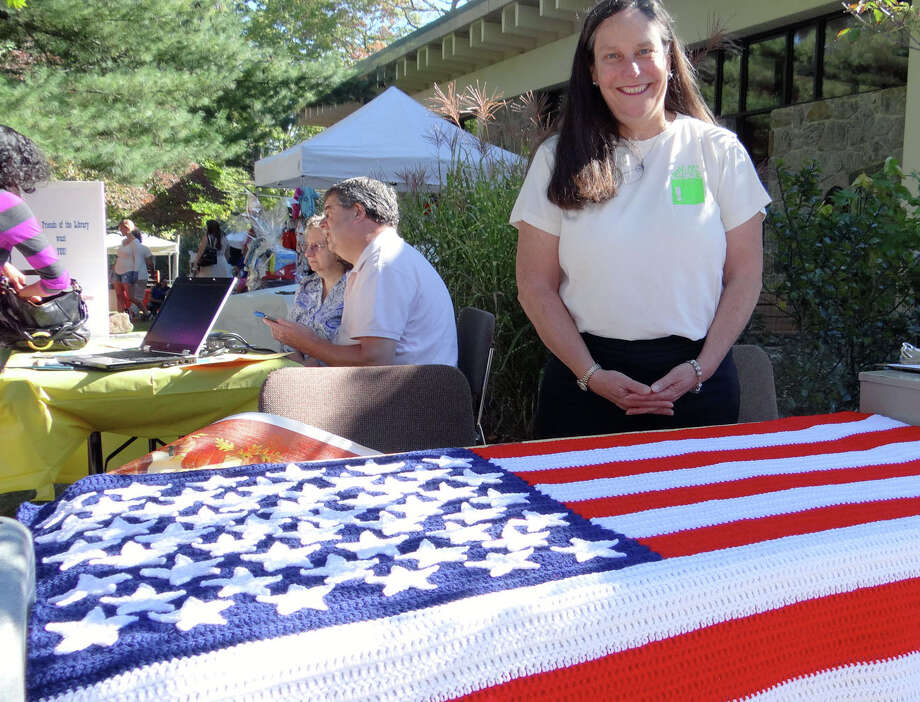 Anne Farkas sells raffle tickets for a crocheted American flag created by Joan Rando at the Fairfield Woods Branch Library's 45th birthday celebration Saturday. Photo: Mike Lauterborn / Westport News