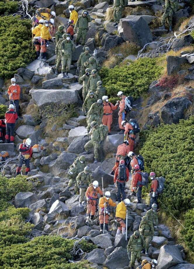 Firefighters and members of the Japan Self-Defense Forces descend Mount Ontake after they called off a search operation due to noxious fume in central Japan, Sunday, Sept. 8, 2014. Mount Ontake erupted shortly before noon Saturday, spewing large white plumes of gas and ash high into the sky and blanketing the surrounding area in ash. Rescue workers have found 30 or more people unconscious and believed to be dead near the peak of an erupting volcano in central Japan, local government and police said.  JAPAN OUT, MANDATORY CREDIT Photo: Kyodo News, AP / Kyodo News