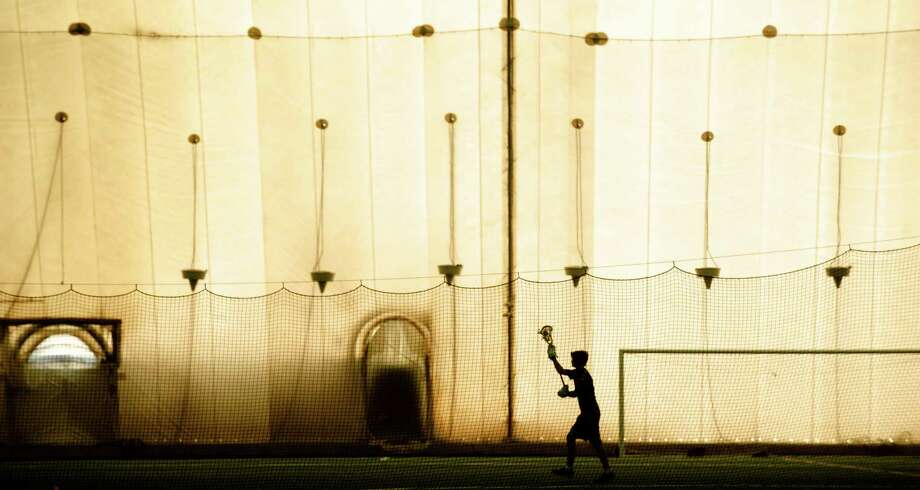 A lacrosse player practices while the sun sets outside the Danbury Sports Dome, on Shelter Rock Road, in Danbury, Conn. Friday, September 26, 2014. Photo: H John Voorhees III / The News-Times Staff Photographer
