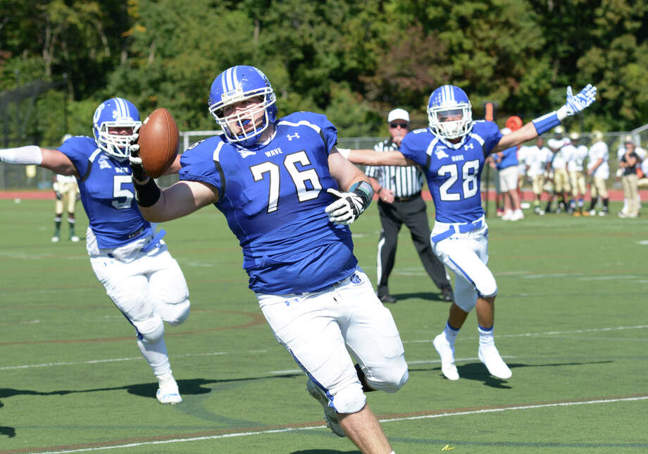 Darien rallies around teammate Jack Griffiths (76) as he carries the ball for a touchdown during the first quarter of a regular-season football game against Bassick at Darien High School on Saturday, Sept. 27. Photo: Amy Mortensen / Connecticut Post Freelance