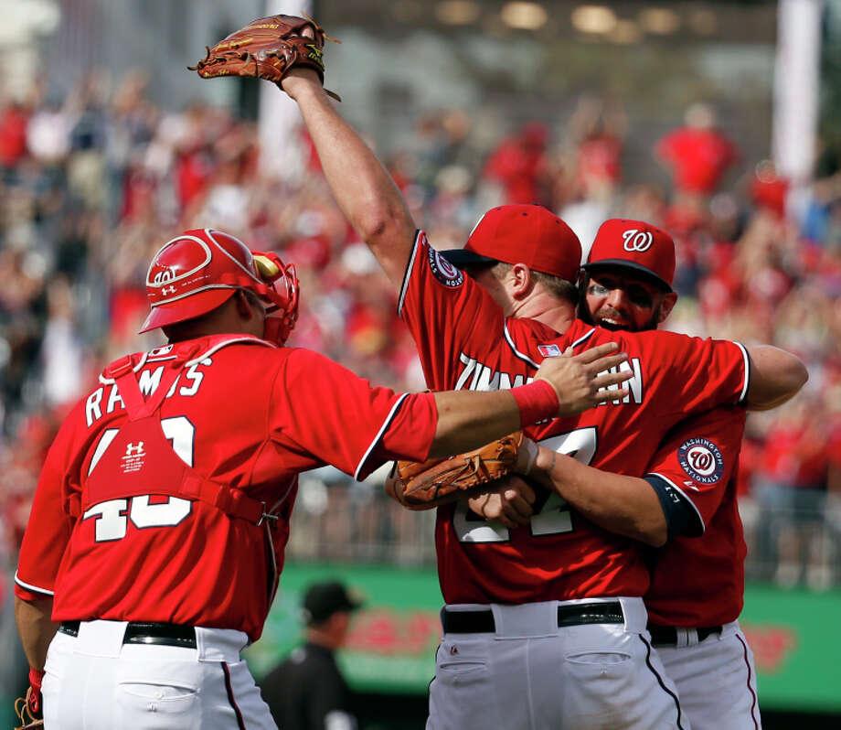 Catcher Wilson Ramos (left) and Kevin Frandsen congratulate Jordan Zimmermann for his no-hitter. Photo: Alex Brandon / Associated Press / AP