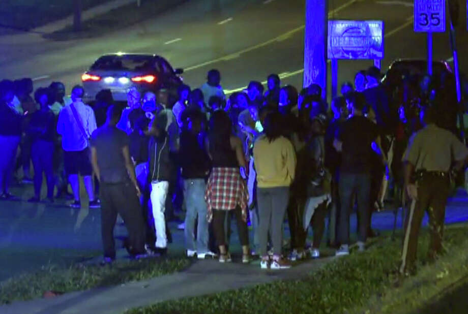 In this framegrab image courtesy of KSDK-TV a crowd gathers near the scene where a police officer was shot in the arm Saturday night Sept. 27, 2014 in Ferguson, Missouri. The officer was shot in the arm and is expected to survive, St. Louis County Police Chief Jon Belmar said. (AP Photo/KSDK-TV) Photo: Associated Press / KSDK-TV