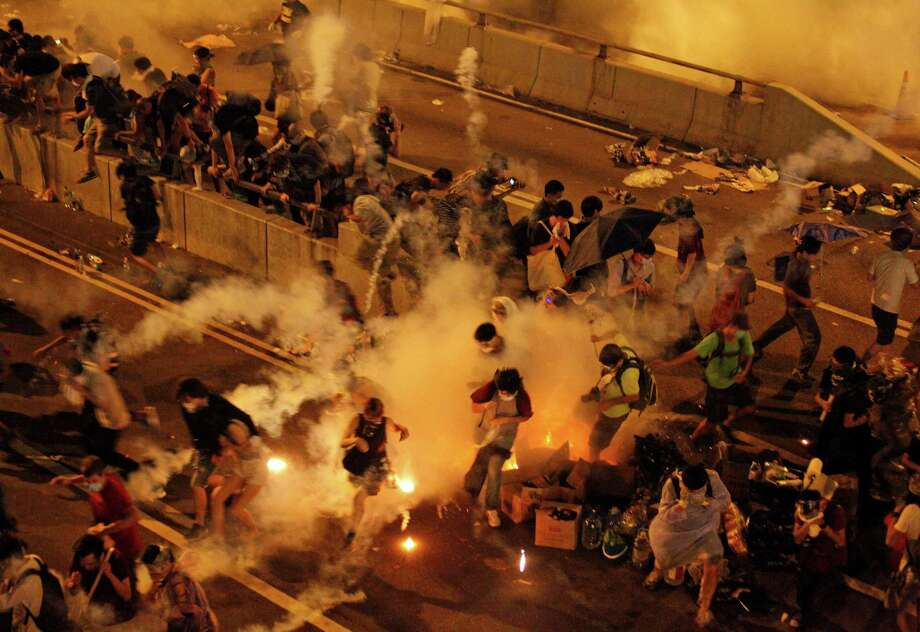 Riot police use tear gas to try to clear thousands of pro-democracy protesters who blocked a main road at the financial central district in Hong Kong. Photo: Associated Press / ap