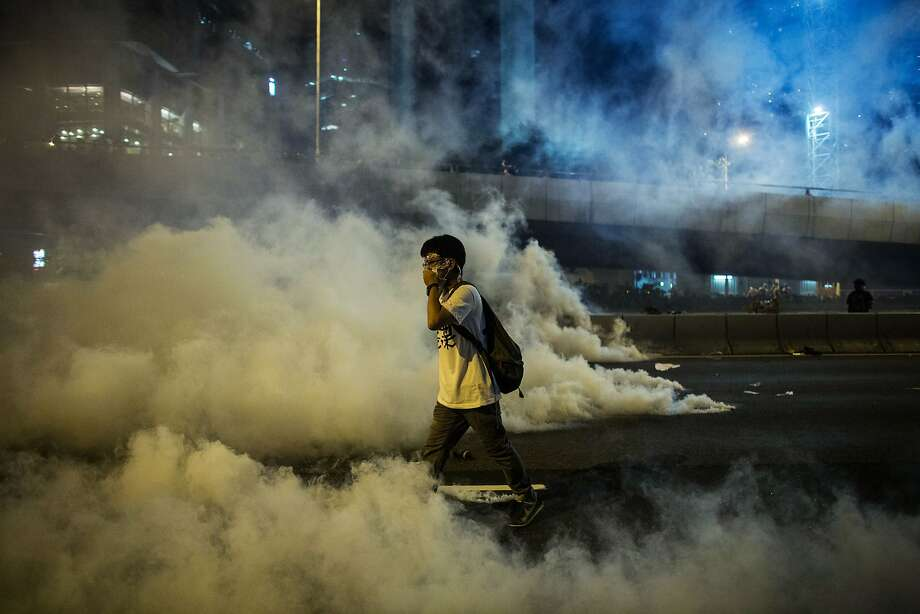 A demonstrator covers his nose and mouth as he walks through tear gas fired by police during a protest near central government offices in Hong Kong, China, on Sunday, Sept. 28, 2014. Thousands of Hong Kong pro-democracy demonstrators defied tear gas and pepper spray to occupy the city center, as police undertook the biggest crackdown since the city returned to Chinese rule. Photographer: Lam Yik Fei/Bloomberg Photo: Lam Yik Fei, Bloomberg
