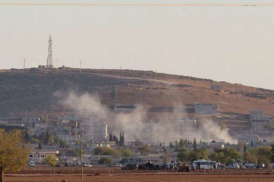 Smoke rises from the Syrian Kurdish town of Kobani after an explosion as Islamic State militants advance on the town full of Syrian refugeees. Photo: Carsten Koall / Getty Images / 2014 Getty Images