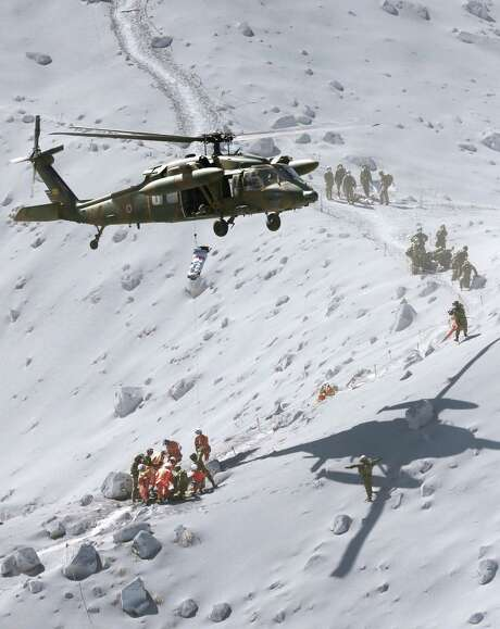 A helicopter from the Japan Ground Self-Defense Force hovers over Mount Ontake to rescue climbers around the peak of the mountain in central Japan. Mount Ontake erupted shortly before noon Saturday, spewing large plumes of gas and ash high into the sky. Rescue workers have found 31 bodies so far. Photo: Associated Press / Kyodo News