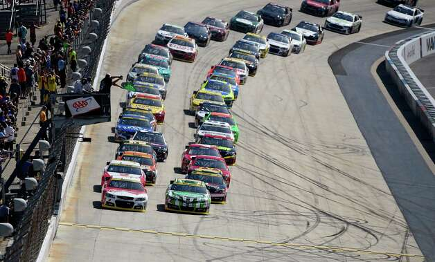 The field led by Kevin Harvick, left front, and Kyle Busch, right front, takes the green flag for the start of the NASCAR Sprint Cup series auto race, Sunday, Sept. 28, 2014, at Dover International Speedway in Dover, Del. (AP Photo/Nick Wass) ORG XMIT: DOV101 Photo: Nick Wass / FR67404 AP
