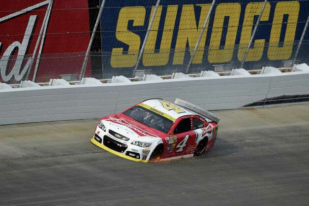 Sparks fly from the car of Kevin Harvick as a tire starts to go down during the NASCAR Sprint Cup series auto race, Sunday, Sept. 28, 2014, at Dover International Speedway in Dover, Del. (AP Photo/Nick Wass) ORG XMIT: DOV102 Photo: Nick Wass / FR67404 AP