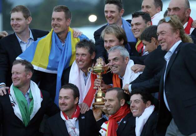 Europe team captain Paul McGinley, center right, and his team wear their national flags and celebrate with the trophy after winning the Ryder Cup golf tournament at Gleneagles, Scotland, Sunday, Sept. 28, 2014. (AP Photo/Scott Heppell) ORG XMIT: RCUP317 Photo: Scott Heppell / AP