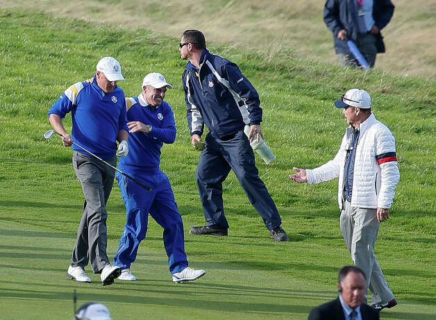 US team captain Tom Watson, right, congratulates Europe team captain Paul McGinley and Jamie Donaldson, left, after winning the Ryder Cup golf tournament during the singles match on the final day of the  at Gleneagles, Scotland, Sunday, Sept. 28, 2014. (AP Photo/Alastair Grant) ORG XMIT: RCUP203 Photo: Alastair Grant / AP