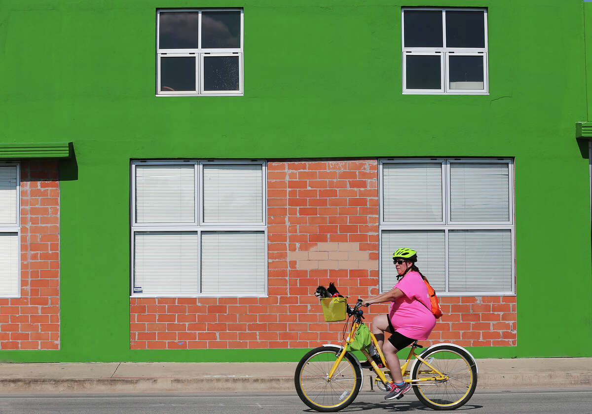 A woman and her pets ride along Broadway street during this year's Siclovia, Sunday, Sept. 28, 2014. More than 65,000 are expected to participate in the event that has been extend into the east side to Dignowity and Lockwood Parks.