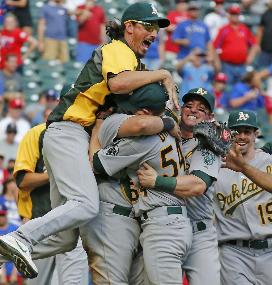 Oakland A's pitcher Jeff Samardzija, left, and other teammates embrace starting pitcher Sonny Gray after the final out in their wild card-clinching 4-0 win during the Oakland Athletics vs. the Texas Rangers major league baseball game at Globe Life Park in Arlington on Sunday, September 28, 2014.    (AP Photo/The Dallas Morning News, Louis DeLuca)  MANDATORY CREDIT; MAGS OUT; TV OUT; INTERNET USE BY AP MEMBERS ONLY; NO SALES Photo: Louis DeLuca, Associated Press