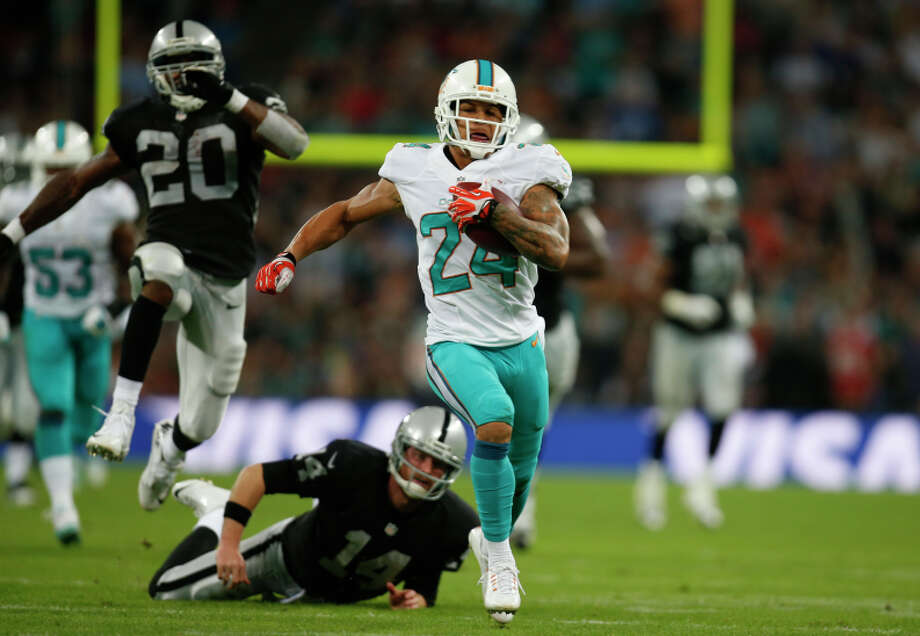 Dolphins defensive back Cortland Finnegan returns a fumbled snap for a touchdown during the second half. Photo: Lefteris Pitarakis / Associated Press / AP