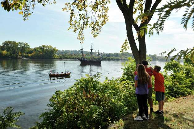 Ron Katchmar and his step-children, Abby Eichmann, 10, and Dylan Eichmann, 12, watch re-enactors row a boat down the Hudson River past the ship the Half Moon  at the Corning Preserve during the Early Albany: A Hudson River Festival event on Sunday, Sept. 28, 2014, in Albany, N.Y.  The ship is a full-scale, operating replica of the Dutch ship of exploration that Henry Hudson sailed up the Hudson River in 1609.   A historical encampment was created on the banks of the Hudson River where visitors could see demonstrations on how Dutch settlers and the Native Americans in the area lived and worked during the early 1600's.  This year was also the 15th annual Fall of Voyage of Discovery, a trip where local school children and Dutch school children sailed the ship up the river, conducting science experiments along the way.    (Paul Buckowski / Times Union) Photo: Paul Buckowski / 00028422A