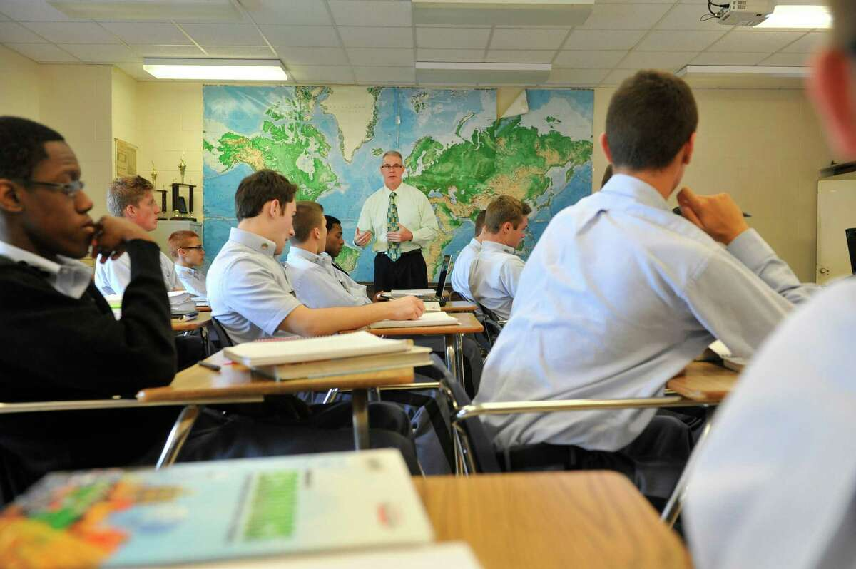 Kenneth Bentley teaches an economics class at LaSalle Institute on Wednesday, Sept. 17, 2014, in Troy, N.Y. The school is doing away with the Regents exams for students in grades 9-12. (Paul Buckowski / Times Union)