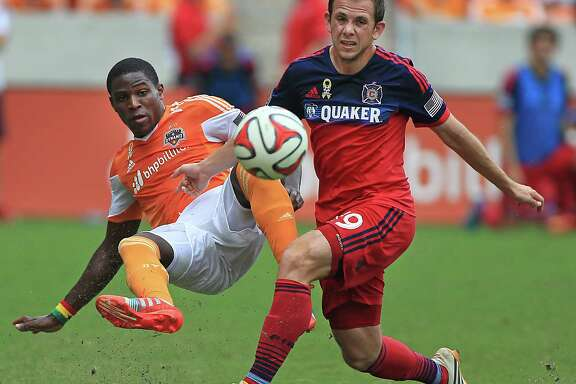 The Dynamo's Luis Garrido left, goes airborne after clearing the ball away from the Fire's Harry Shipp.