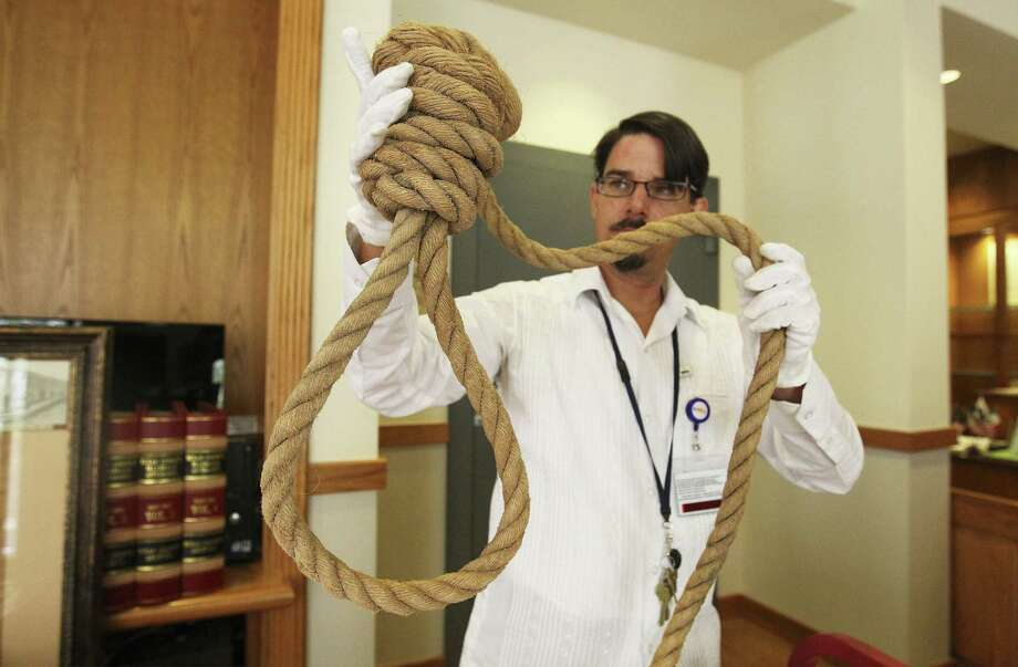 Spanish archivist David Carlson holds up a hangman's noose believed to have been in use from around the 1890s to the 1920s in Bexar County. The Bexar County Archives Center mostly keeps documents, records and maps, he said. Photo: Photos By Kin Man Hui / San Antonio Express-News / ©2014 San Antonio Express-News