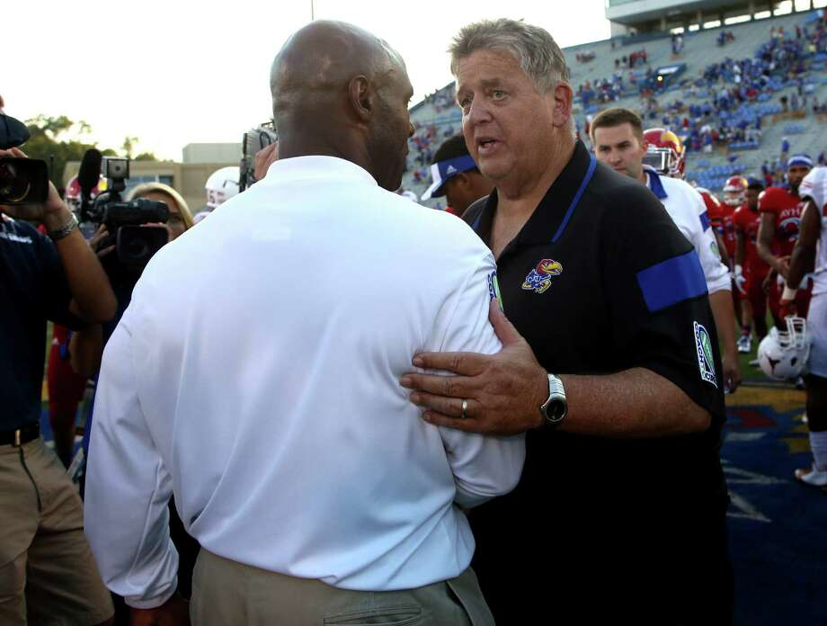 Kansas coach Charlie Weis (right) was fired Sunday, a day after coach Charlie Strong and Texas shut out the Jayhawks. Weis went 6-22 with Kansas. Photo: Ed Zurga / Associated Press / FR34145 AP