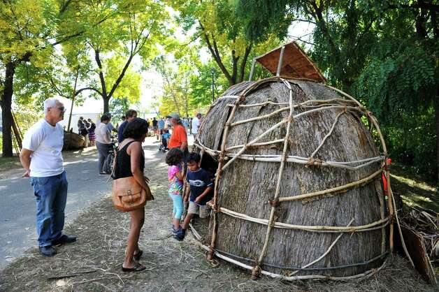 Visitors look over a Native American wigwam house at the Corning Preserve during the Early Albany: A Hudson River Festival event on Sunday, Sept. 28, 2014, in Albany, N.Y.  A historical encampment was created on the banks of the Hudson River where visitors could see demonstrations on how Dutch settlers and the Native Americans in the area lived and worked during the early 1600's.      (Paul Buckowski / Times Union) Photo: Paul Buckowski / 00028422A