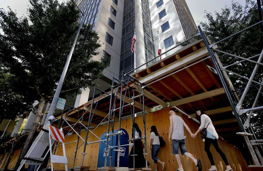 The exterior has been surrounded by roofed scaffolding to protect pedestrians in case any more window fall from above, which has happened in the past at the California State Board of Equalization Board headquarters building in downtown Sacramento, Calif., as seen on Friday Sept. 26, 2014. The California State Board of Equalization headquarters in down town Sacramento has a long history of problems since the high rise was built 22 years ago- mold, flooding, fee falling elevators and falling windows to name a few. Photo: Michael Macor, The Chronicle