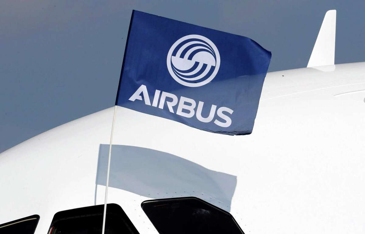 A flight test engineer holds an Airbus Group flag after the first flight of the Airbus A320neo