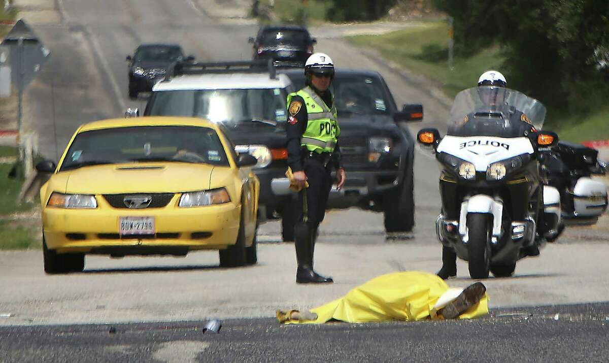 San Antonio police officers investigate at accident involving an 18 wheeler truck and a motorcyclist on Northwest Military Highway under 1604 Monday, Sept. 29, 2014. The motorcyclist died at the scene.