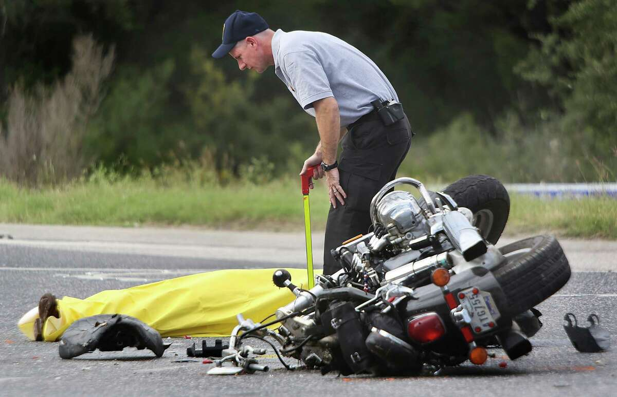 A San Antonio police officer investigates an accident involving an 18 wheeler truck and a motorcyclist on Northwest Military Highway under 1604 Monday, Sept. 29, 2014. The motorcyclist died at the scene.