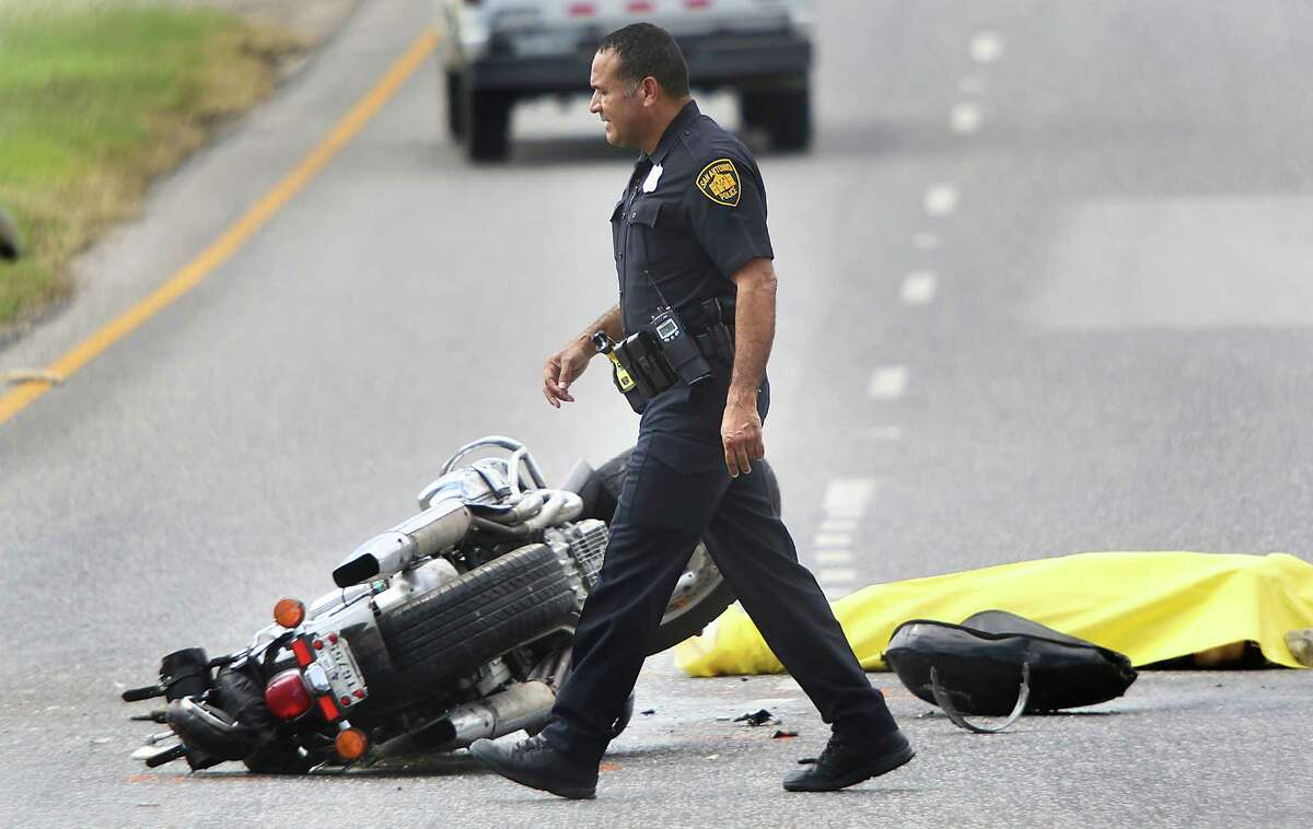 San Antonio police officers investigate an accident involving an 18 wheeler truck and a motorcyclist on Northwest Military Highway under 1604 Monday, Sept. 29, 2014. The motorcyclist died at the scene.