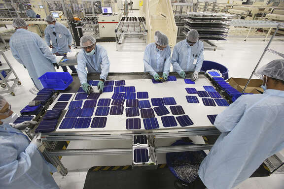 During a break in the automatic production, employees gather Sept. 17 to reconstruct one of the damaged panels as Mission Solar produces solar panels at its Brooks City-Base location.