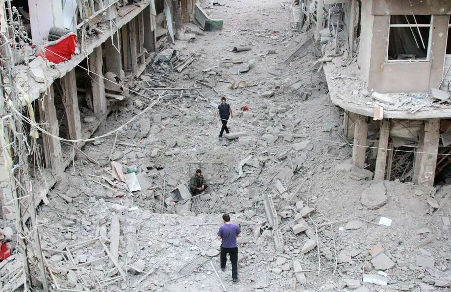 People walk on the rubble of damaged buildings after a Syrian military helicopter allegedly droped barrel bombs over the city of Daraya, southwest of the capital Damascus. Photo: FADI DIRANI / AFP/Getty Images / AFP