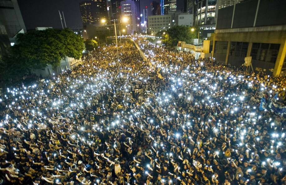 Thousands of demonstrators in Hong Kong hold up cell phones in solidarity for democratic voting rights. Photo: XAUME OLLEROS / AFP/Getty Images / AFP