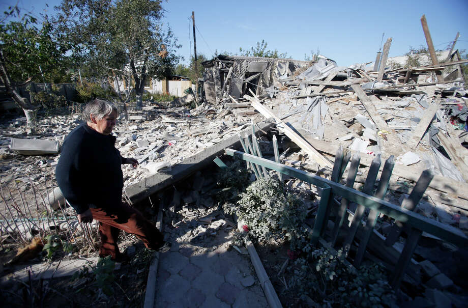 A woman observes damage at a destroyed home after shelling in the town of Donetsk in eastern Ukraine. Photo: Darko Vojinovic / Associated Press / AP