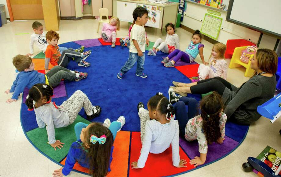 Lucas Crespo stands in the middle of the carpet as students stop their feet while listening to a song about dinosaurs during preschool at Roxbury Elementary School on Wednesday, September 24, 3014. Photo: Lindsay Perry / Stamford Advocate