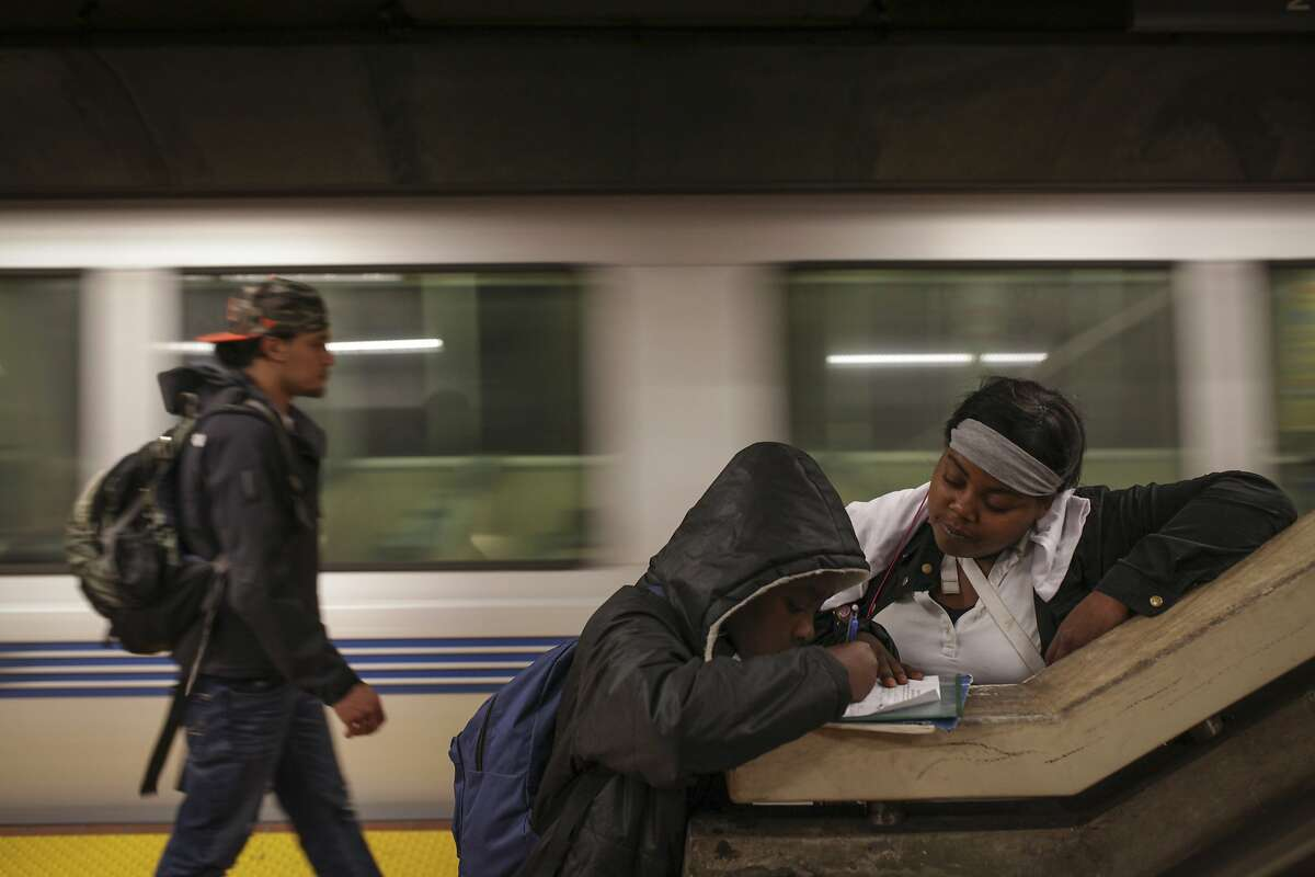 Ashley Jordan helps Damarco Reed with his english homework while waiting for one of the last BART trains back to the East Bay at the 24th Street BART station in San Francisco on September 29th 2014.