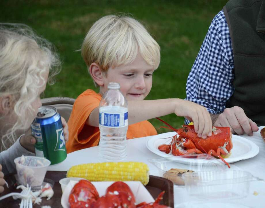Graham Ernst enjoys a lobster dinner on the grounds of the New Canaan Historical Society, New Canaan, Conn., during the 29th annual New Canaan Family Lobsterfest on Friday, Sept. 26, 2014. Photo: Nelson Oliveira / New Canaan News